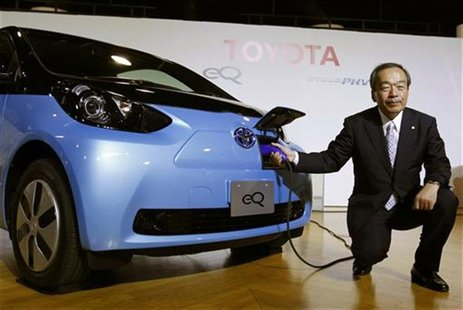 Toyota Motor Corp's Executive Vice President Takeshi Uchiyamada poses next to the company's newly developed compact electric vehicle eQ afte