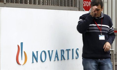 An employee smokes a cigarette beside the logo of Swiss drugmaker Novartis AG in front of a plant in Basel October 25, 2011. REUTERS/Arnd Wi
