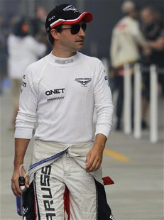Marussia Formula One driver Timo Glock of Germany walks in the pit lane before the first practice session of the Indian F1 Grand Prix at the