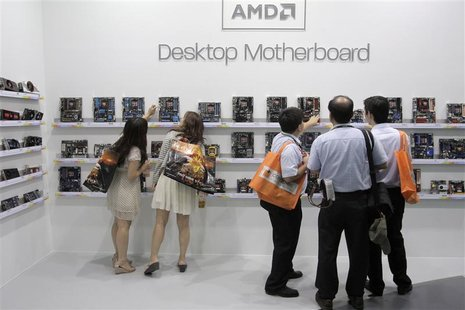 Visitors look at motherboards being displayed at the AMD booth during the 2012 Computex exhibition at the TWTC Nangang exhibition hall in Ta