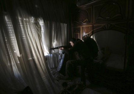 A fighter from the Sadik unit of Free Syrian Army's Tahrir al Sham brigade takes aim at Syrian soldiers position from a house in Mleha subur
