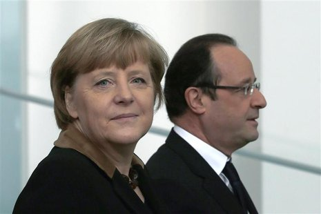 German Chancellor Angela Merkel (L) and French President Francois Hollande leave a family picture opportunity at the chancellery in Berlin d