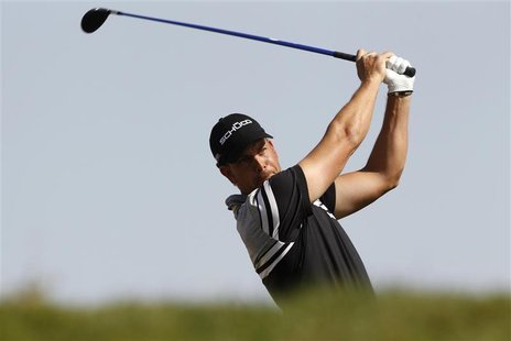 Henrik Stenson of Sweden tees off at the third hole during the first round of the Abu Dhabi Golf Championship at the Abu Dhabi Golf Club Jan