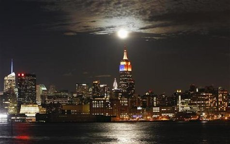 A full moon rises behind the Empire State Building and the skyline of New York, as seen from a park along the Hudson River in Hoboken, New J