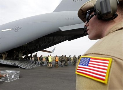 A U.S. soldier looks on as French soldiers leave a U.S. Air Force C-17 transport plane in Bamako January 22, 2013. The United States has sta