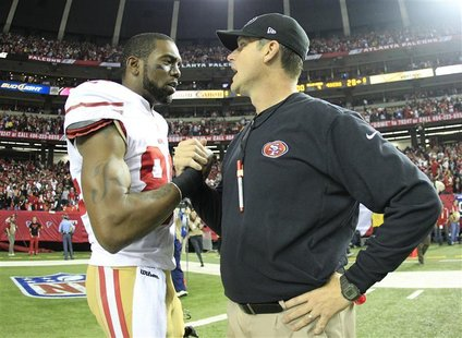 San Francisco 49ers wide receiver Randy Moss (L) shakes hands with head coach Jim Harbaugh after the 49ers defeated the Atlanta Falcons to w