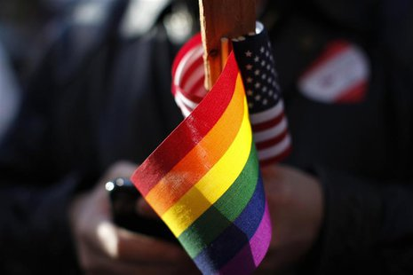 Marriage equality supporter Gus Thompson holds gay pride and American flags at a demonstration outside the appeals hearing on California?s P