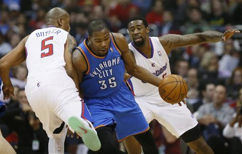 Oklahoma City Thunder's Kevin Durant (C) is fouled by Los Angeles Clippers Caron Butler (L) as the Clippers DeAndre Jordan looks on during t
