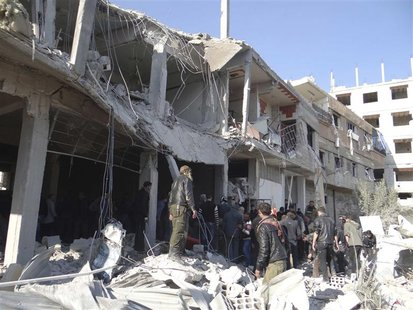 Free Syrian Army fighters and residents are seen near buildings damaged after what activists say were missiles fired by Syrian Air Force fig
