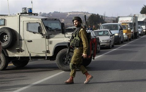 An Israeli soldier walks in front of a military vehicle blocking traffic on a road near the scene of a shooting in al-Arroub refugee camp ne