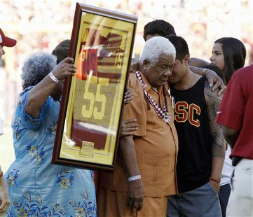 Family members hold up a No. 55 jersey as part of a ceremony held in memory of the late former USC Trojans, San Diego Chargers and NFL lineb