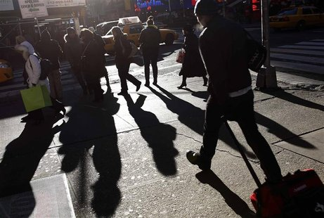 People walk in the late afternoon sun through Times Square in New York January 22, 2013. REUTERS/Carlo Allegri