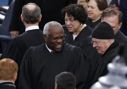 U.S. Supreme Court Justice Clarence Thomas (C) arrives with fellow Court members for inauguration ceremonies on the West front of the U.S. C