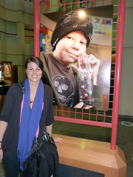 Jess Kelley in front of the picture of the young boy holding his legacy beads. These beads represent a procedure, therapy or medication the child has completed in treatment - the picture speaks for itself - that little guy has been through a lot.
