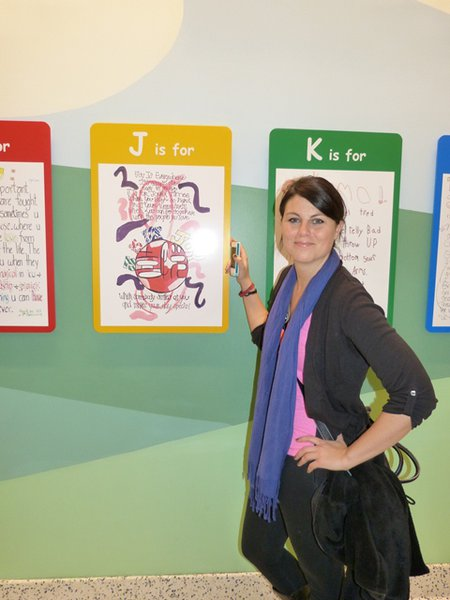 Jess Kelley in front of the Alphabet of Cancer wall.