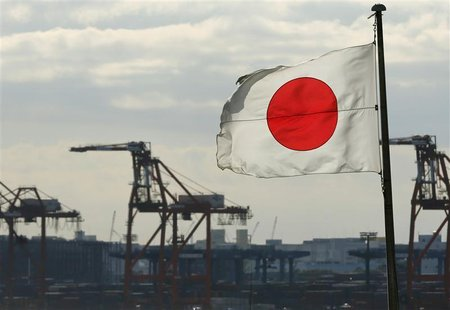 A Japanese flag flutters in front of a shipping container area, at a port in Tokyo December 19, 2012. REUTERS/Yuriko Nakao