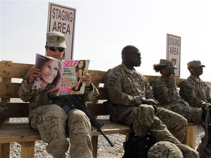 U.S. Army soldier SSG Norma Gonzales of 426 Civil Affairs Battalion reads a magazine while waiting to be ferried by a helicopter to differen