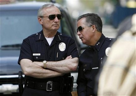 Los Angeles police chief William Bratton (L) stands next to an unidentified officer as people take part in a May Day protest march for immig