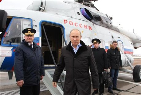 Russian President Vladimir Putin (C) arrives at the town of Krymsk in the Krasnodar region January 11, 2013. REUTERS/Mikhail Klimentyev/RIA