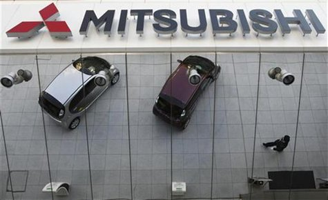 Mitsubishi Motors Corp's vehicles and a passer-by are reflected on an external wall at the company headquarters in Tokyo January 20, 2011. R