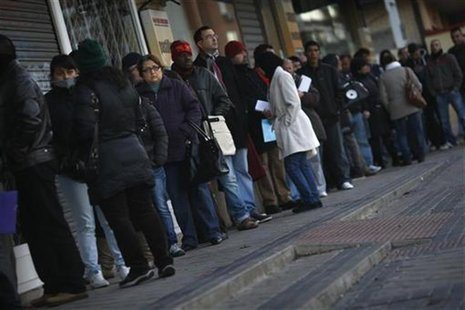 People wait in line to enter a government-run employment office in Madrid January 3, 2013. REUTERS/Susana Vera