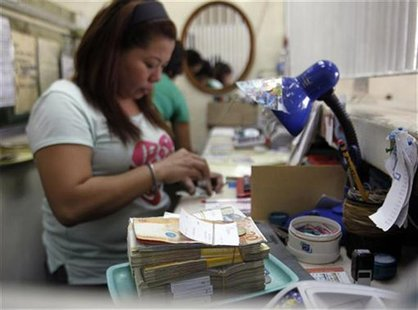 A woman counts peso bills at a currency exchange office in Manila September 26, 2012. REUTERS/Cheryl Ravelo