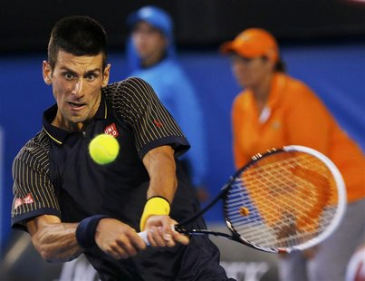 Novak Djokovic of Serbia hits a return to David Ferrer of Spain during their men's singles semi-final match at the Australian Open tennis to