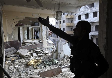 A Free Syrian Army fighter gestures in a building damaged by Syrian Army tank shells in the Arabeen neighbourhood of Damascus January 24, 20