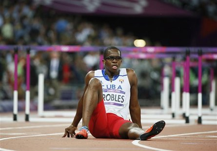 Cuba's Dayron Robles sits on the track after he suffered an injury during the men's 110m hurdles final during the London 2012 Olympics Games