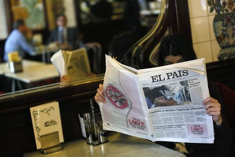 A woman poses with a copy of the January 24 first edition of Spanish newspaper El Pais in a cafe in central Madrid January 24, 2013. REUTERS