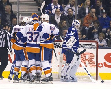 The New York Islanders celebrate next to Toronto Maple Leafs' goalie Ben Scrivens after Islanders Brad Boyes scored in the second period of