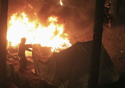 Riot police set fire to tents pitched by anti-Mursi demonstrators at Tahrir Square in Cairo January 25, 2013. REUTERS/Mohamed Abd El Ghany