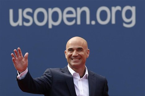 Two-time U.S. Open champion Andre Agassi waves before being inducted into the U.S. Open Court of Champions, which celebrates the legacy of t