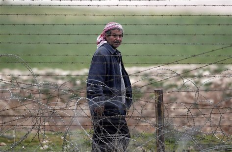 A man from the northern Syrian town of Ras al-Ain walks along the border fence as he is pictured from the Turkish border town of Ceylanpinar