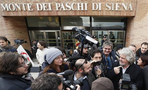 Five-Star Movement activist and comedian Beppe Grillo (R) talks to the media as he leaves the shareholders meeting at Banca Monte dei Paschi