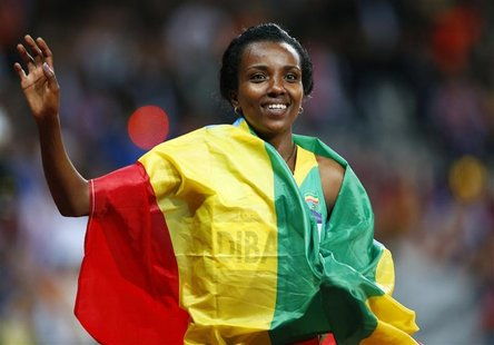 Ethiopia's Tirunesh Dibaba, with her national flag, waves after she won the women's 10,000m final at the London 2012 Olympic Games at the Ol