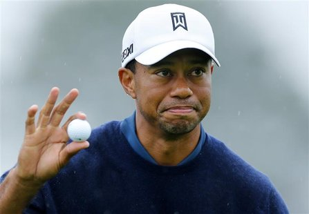 U.S. golfer Tiger Woods holds up his ball after making a birdie to end his round 11-under par during second round play at the Farmers Insura
