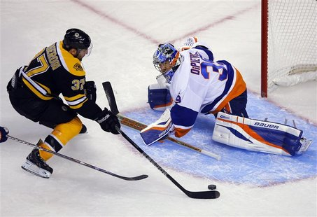 Boston Bruins' center Patrice Bergeron (L) scores a goal against New York Islanders' goaltender Rick DiPietro in the third period of their N