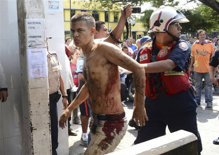 A rescue worker walks with an unidentified injured man during an uprising at the Centro Occidental (Uribana) prison in Barquisimeto in this