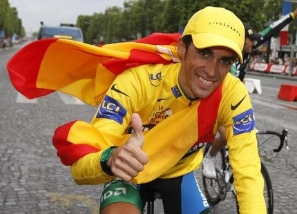 Discovery Channel team rider Alberto Contador of Spain, overall winner, cycles up the Champs Elysees to celebrate his victory after the fina