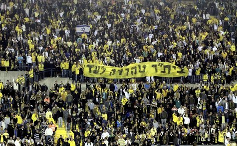"Supporters of Beitar Jerusalem soccer club hold a banner reading ""Beitar will always remain pure"" during a Premier League match in Jerusalem"