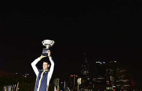 Novak Djokovic of Serbia poses with the Norman Brookes Challenge Cup after defeating Andy Murray of Britain in their men's singles final mat