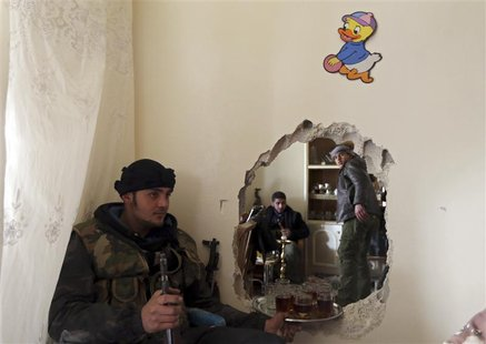 A fighter from the Free Syrian Army's Tahrir al Sham holds tray of tea in Mleha suburb of Damascus January 27, 2013. REUTERS/Goran Tomasevic