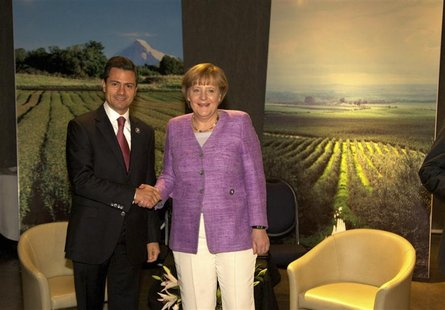 Mexico's President Enrique Pena Nieto (L) shakes hands with Germany's Chancellor Angela Merkel during a private meeting at summit of the Com