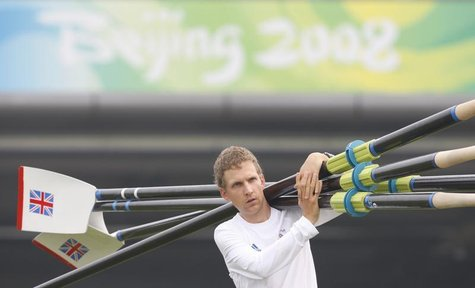 Britain's Men's Eight rowing coxman Acer Nethercott carries oars to the water for a training session at Shunyi Olympic Rowing-Canoeing Park