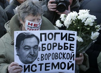 A woman holds a placard with a portrait of Sergei Magnitsky during an unauthorised rally in central Moscow December 15, 2012. REUTERS/Tatyan