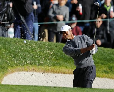 U.S. golfer Tiger Woods hits from a sand trap on the 18th green during weather delayed third round play at the Farmers Insurance Open in San