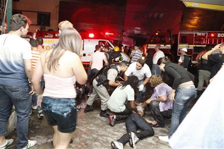 A policeman and rescue workers help a man in front of Kiss nightclub in the southern city of Santa Maria, 187 miles (301 km) west of the state capital of Porto Alegre, in this picture taken by Agencia RBS, January 27, 2013. REUTERS/Germano Roratto/Agencia RBS