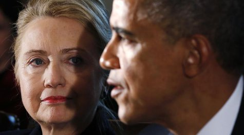 U.S. Secretary of State Hillary Clinton (L) listens to U.S. President Barack Obama speak during a meeting with members of his cabinet at the