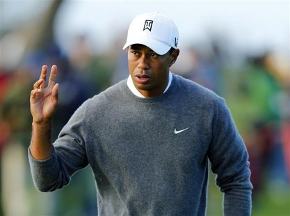 U.S. golfer Tiger Woods waves to fans after making par on the fifth hole during the weather-delayed fourth round play at the Farmers Insuran